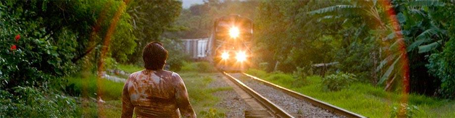 Una patrona attende vicino ai binari il passaggio del treno.