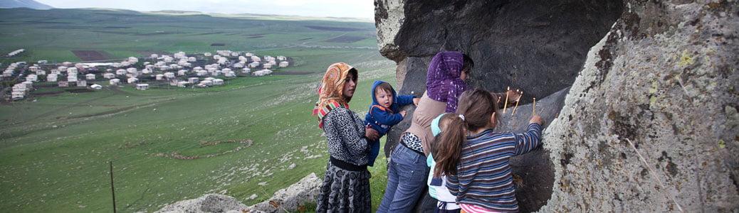 Georgia, Samtskhe-Javakheti. Bambini armeni del villaggio di Kumurdo accendono candele presso una roccia