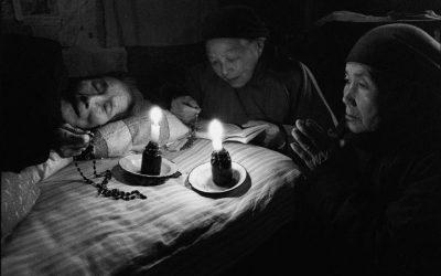 Nel Rosario c'è la storia della Chiesa universale. Cina, Shandong, 1993. Hu-Yu Lan, 89 anni, consacrata, ormai immobilizzata a letto, recita il Rosario con le nipoti, anch'esse cattoliche. © Lu Nan.
