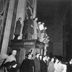 Roma, 25 dicembre 1944. Fedeli arrampicati sui confessionali per assistere alla Messa di mezzanotte celebrata da papa Pio XII in San Pietro.