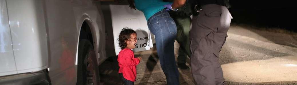McAllen, Texas, 12 giugno 2018. Una bambina di due anni, richiedente asilo onduregna, piange mentre la madre è perquisita ed in seguito detenuta nei pressi del confine tra Stati Uniti e Messico. © John Moore/Getty Images.